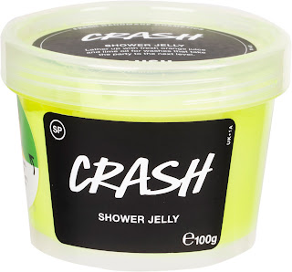 A photo of a cylindrical short clear plastic pot with a green and yellow shower jelly inside with a circular clear lid with a black rectangular black label on the side of the tub with crash shower jelly in white font with a circular black label with lush crash shower jelly in large white font on a bright background