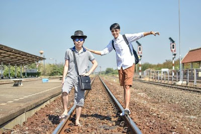 friends standing on train tracks