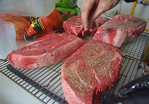 Seasoning meat on racks keeps the seasoning from sticking to the counter or plate.