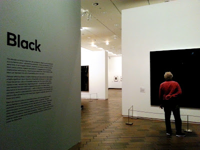 Entrance to an exhibition with the name of it ('Black') on the lefthand wall, with explanation text below. On the right a man in a red shirt is looking at an all-black art work.