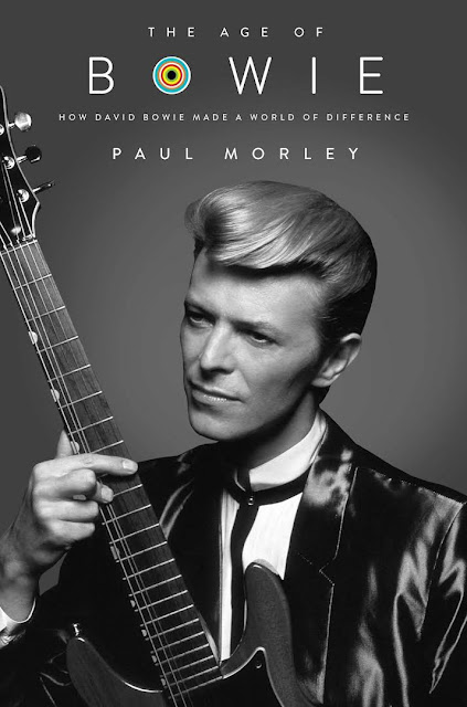 "Image of ""The Age of Bowie"" book cover.  Bowie in dressed in a 90s style tuxedo with guitar in hand."