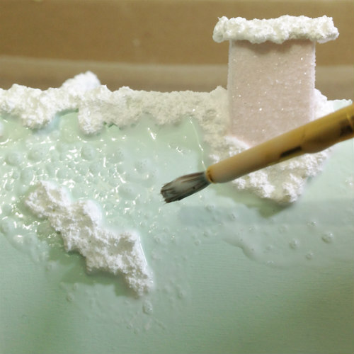using a brush to apply glue to a paper putz house roof
