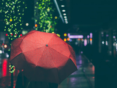 person walking away with red umbrella down rainy nighttime street decorated in small lights