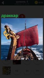 По морю плывет судно драккар под всеми парусами с изображением головы дракона впереди