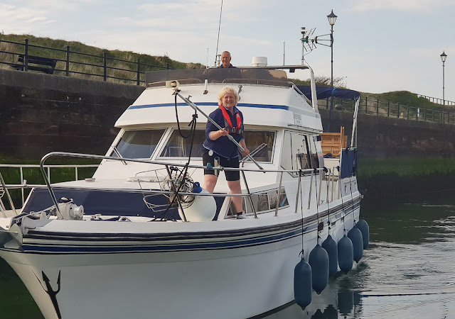 Photo of me holding the boat hook with docking stick ready to hook the cleat