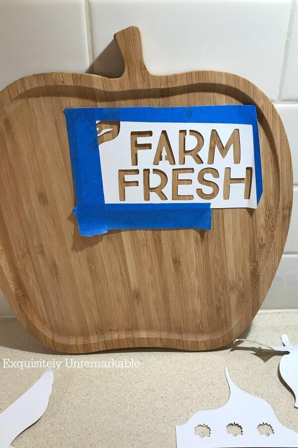 Farm Fresh stencil taped to apple shaped cutting board