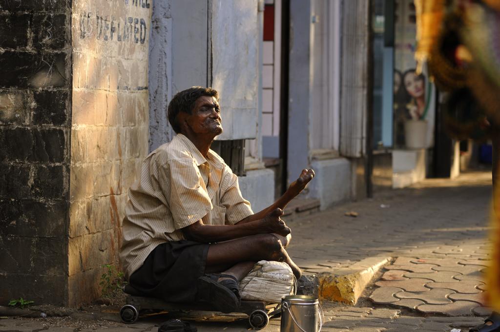 Den tiggende mand er fotograferet i det moderigtige Colaba-distrikt i Mumbai, Indien, hvor tiggere og kvinder med børn under armen tigger om penge til mælkepulver langs butikker og souvenirboder. Dette er en af fotografens mange portrætter af livet fra Indien. Social dokumentarfotografering er optagelsen af, hvordan verden ser ud med et socialt og eller miljømæssigt fokus som i Indien. Det er en form for dokumentarfotografering med det formål at henlede offentlighedens opmærksomhed på igangværende sociale spørgsmål.
