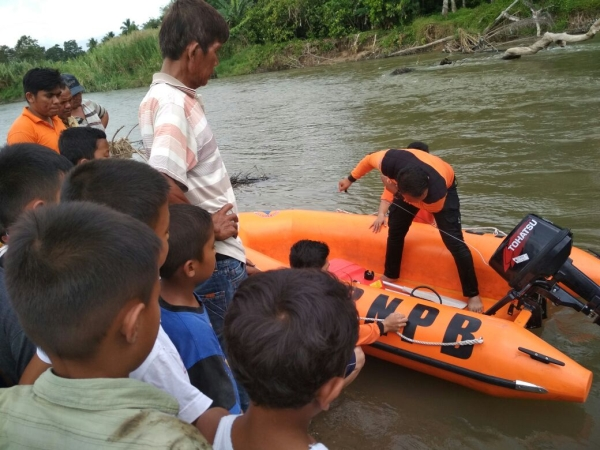 Tim SAR dan warga mencari pendeta yang hanyut di Sungai Batang Gadis.