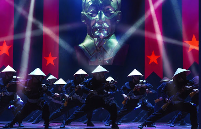 The ensemble perform a dance number as Vietnamese soldiers