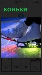 На скамейке сидит человек, на ногах которого одеты коньки из под которых лед светится разными цветами