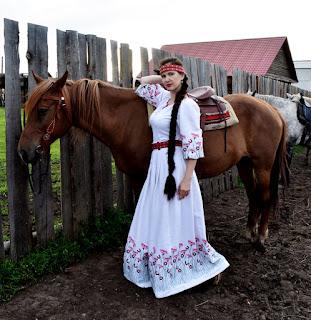 Девушка в славянском платье и лошадь у забора