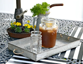 Outdoor table with Metal Tray and Iced tea pitcher and glass.