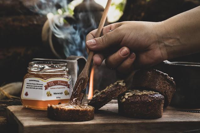 Geleia de Maracujá sendo passado no pão ao lado de uma fogueira