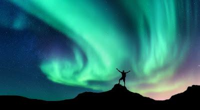 Joven viajando solo con la aurora boreal