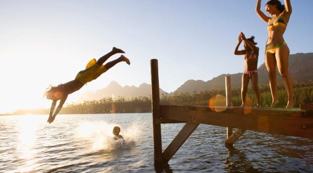 fëmijë duke notuar në liqen