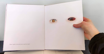 The same spread as the previous image, this time with a hand lifting the page and poking a finger through the hole to show the eye shapes cut out of the page on the right hand side.