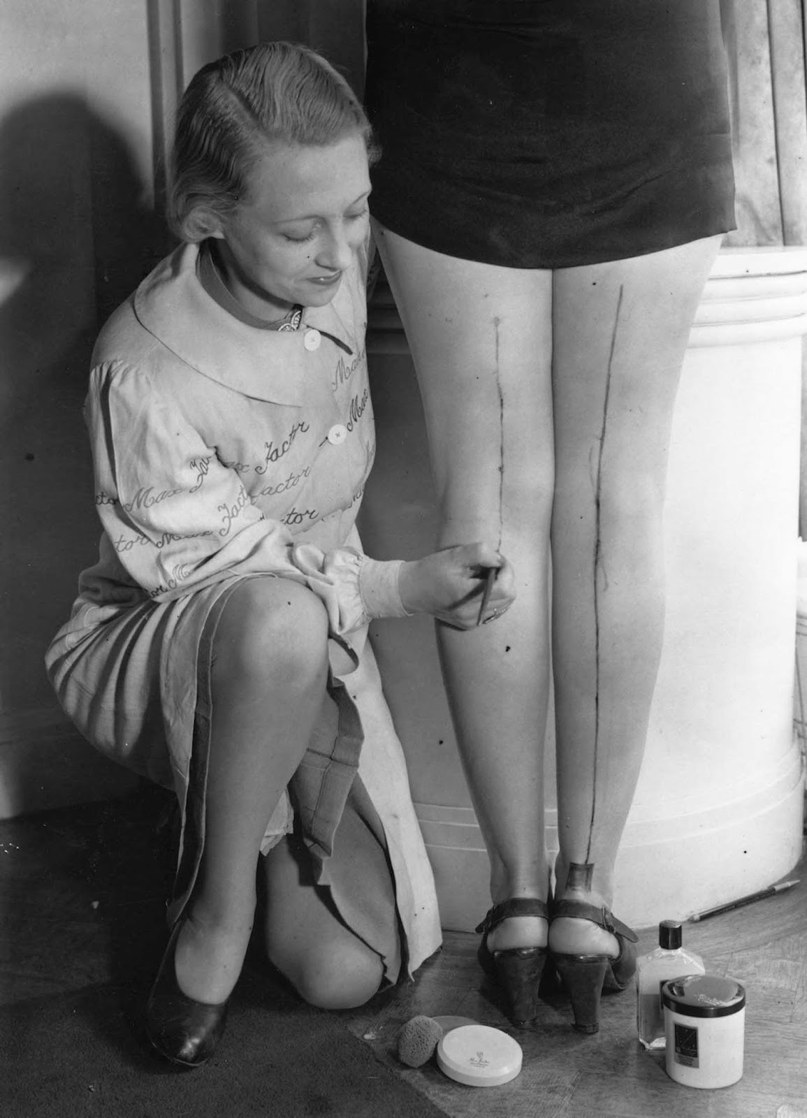 A representative of Max Factor paints cream stockings onto a woman's leg as a solution to the unavailability of stockings during the war.