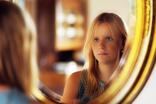 Woman looking in front of a mirror