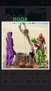 две женщины поднимают воду из колодца и наливают в кувшины
