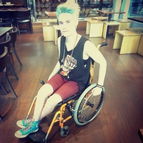 Young woman in wheelchair, with blonde hair highlighted with blue, wearing turquoise Converse high-tops, red shorts, black tank top, sitting in a wheelchair