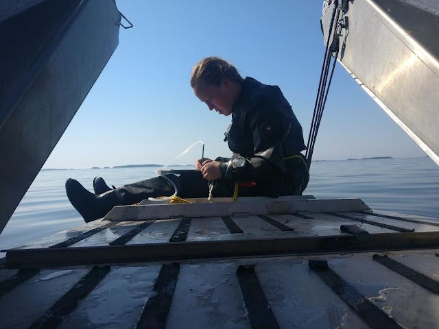Sukeltaja istuu veneen perässä kuivapuvussa.