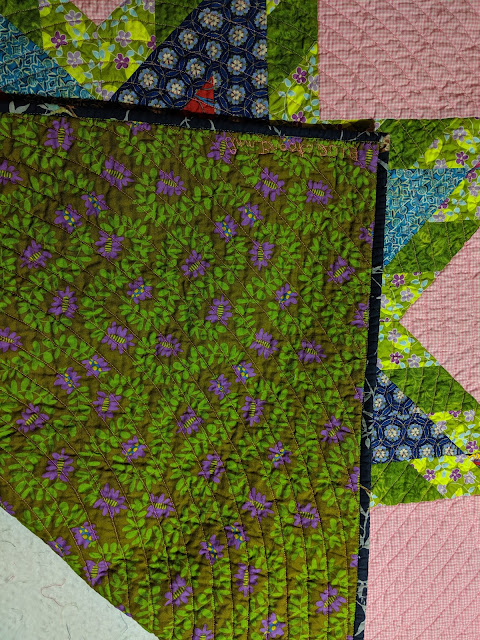 The folded quilt shows front, back, and binding. The back is large purple flowers on olive green and the binding is a navy floral cotton.