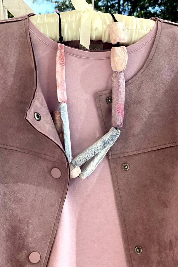 pastel paper mache chunky beaded necklace displayed on clothes hanger with suede jacket and top