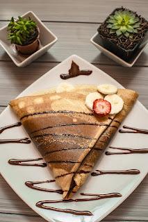 الكريب على شكل مثلث مع خطوط من الشوكولاتة  وشرائح من الموز وقطع من الفراولة