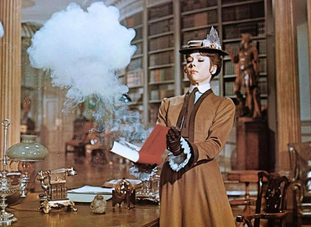 Diana Rigg opening a book with smoke coming out in The Assassination Bureau