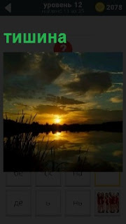 Вечерний закат над озером поражает своей тишиной. Солнце склонилось в закате, отражаясь в воде