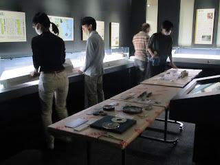 金印関連展示コーナーの大掃除の様子。すべての展示資料をケースから取り出し、普段は手が届かないケースの裏や内側も、学芸員がしっかりと大掃除。