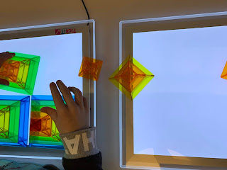 hand reaching over light panel with colorful pyramid shapes