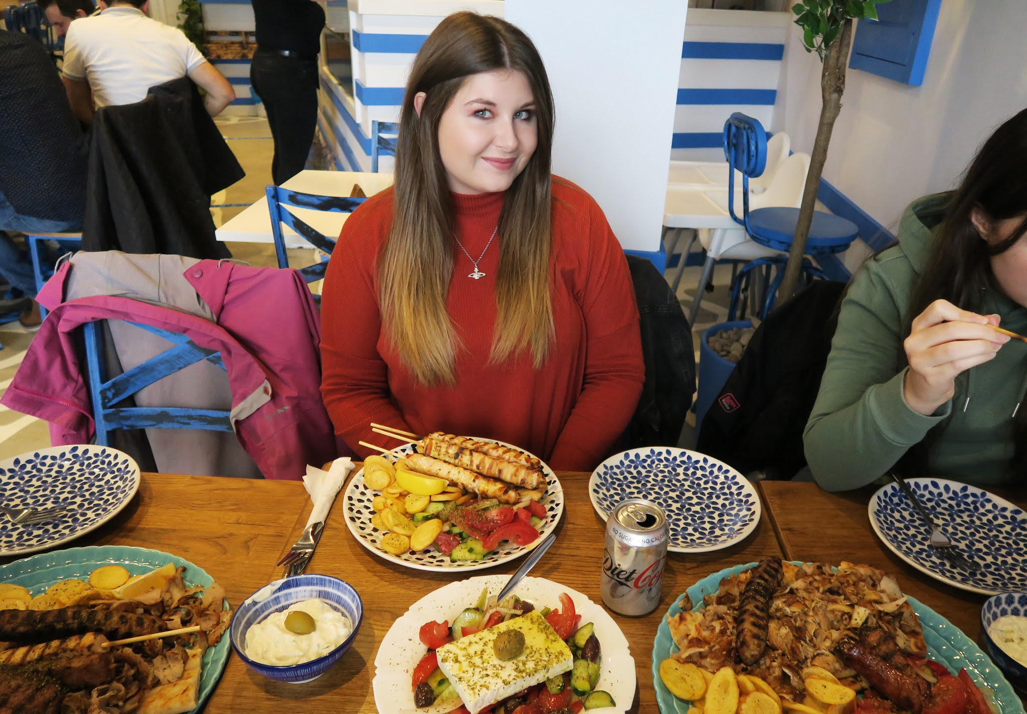 Grace is sat to a table inside Mr Souvlaki Restaurant in Stourbridge. In front of her is a plate of Chicken souvlaki, a bowl of salar, and a mixed grill platter.