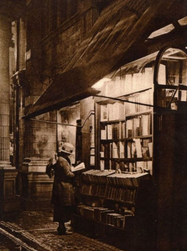 Sepia photo. A young lady looks at a book in the light of at night Sicilian Avenue, London, 1920. Value of Literature marchmatron.com