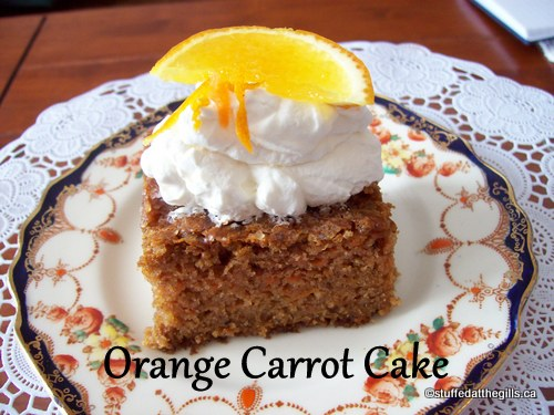 Orange Carrot Cake with a dollop of non-dairy whipped topping garnished with a slice of orange.