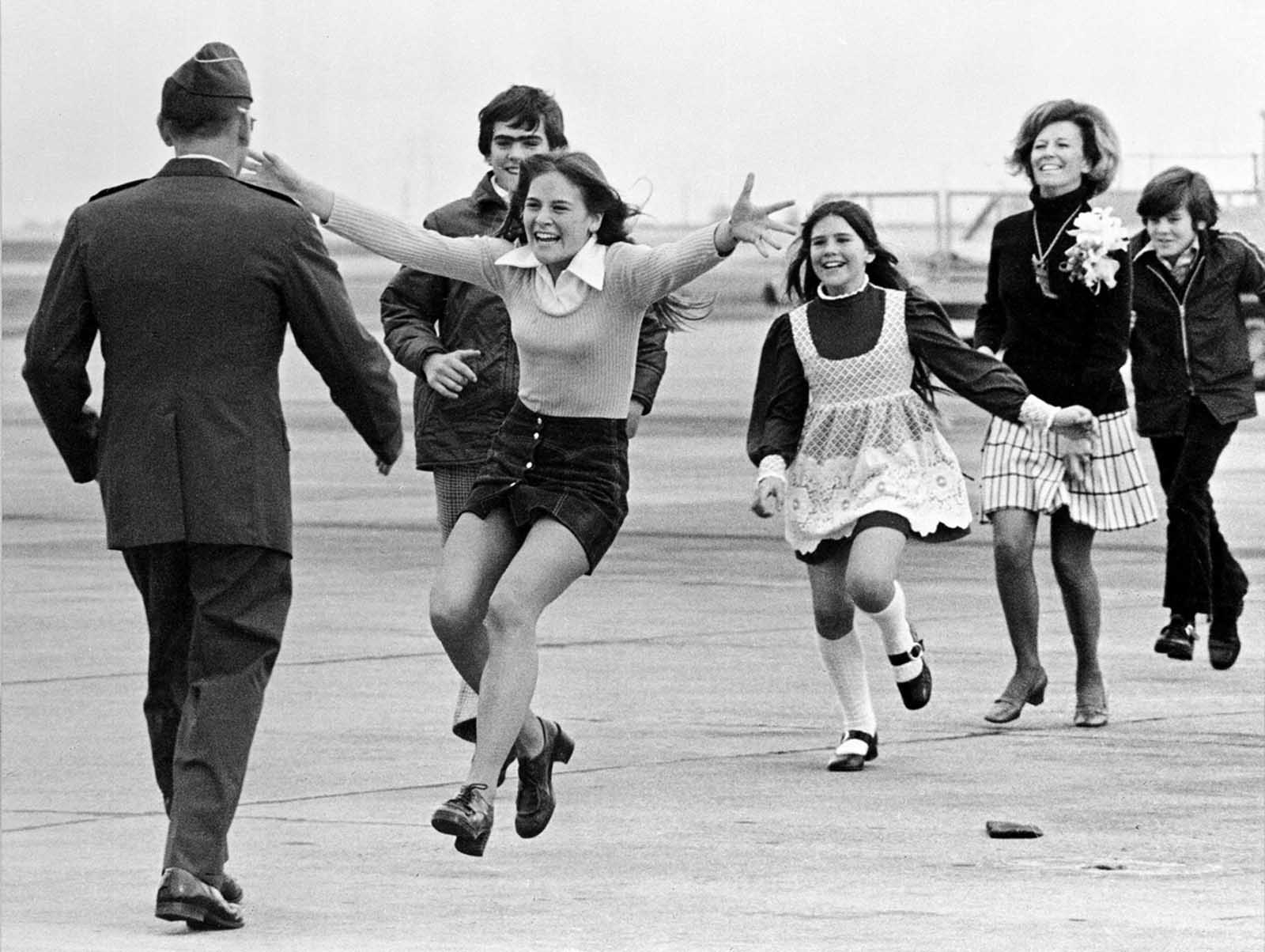 The released prisoner of war Lieutenant Colonel Robert L. Stirm is greeted by his family at Travis Air Force Base in Fairfield, California, as he returns home from the Vietnam War, March 17, 1973. In the lead is Stirm's daughter Lori, 15; followed by son Robert, 14; daughter Cynthia, 11; wife Loretta and son Roger, 12. This famous photo, also called