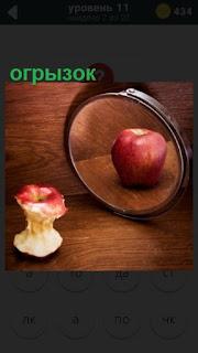 на столе лежит огрызок а в зеркале отражается полное яблоко