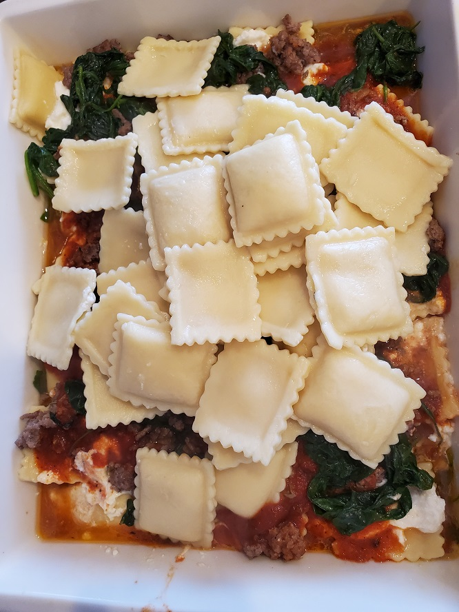 this is a baked casserole with ravioli layered with spinach, cheese and meat