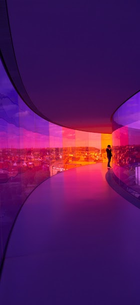 خلفية شخص داخل ممر زجاجي مضاء بألوان بنفسجية