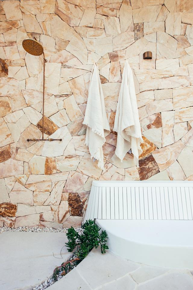 Brass outdoor shower and sandstone accent wall