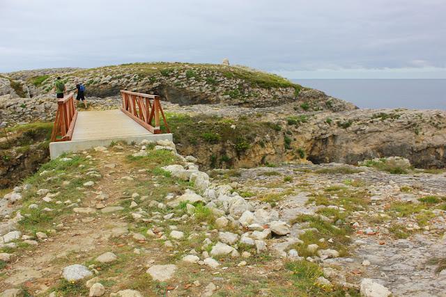 na szlaku turystycznym, łączącym Cabo Mayor w Santander z miejscowością La Maruca. Drewniany most przerzucony nad wąskim urwiskiem, po jego drugiej stronie wędrujący turyści,