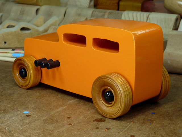 Handmade Wooden Toy Car Hot Rod 1932 Ford Sedan From the Hot Rod Freaky Ford Series Orange & Black Wooden Toys In the Background On Workbench