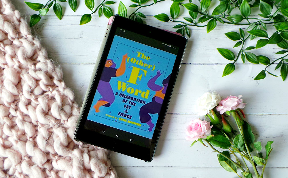 Kindle fire shows the cover of the other f word next to a pink chunky knit blanket, leaves and roses. The cover is blue with the title written in yellow and purple. There are 2 illustrated people dancing on the edges