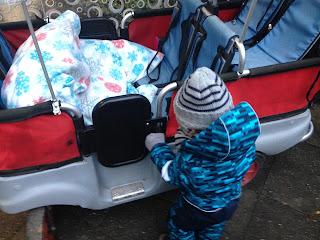 Das Kind steigt selbstständig in den großen Kinderwagen für 6 Personen ein