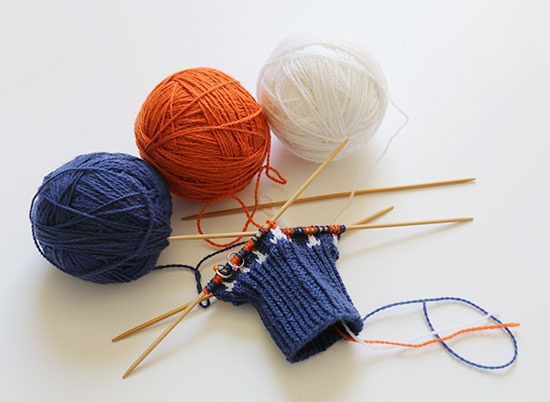 Hand knit blue cuff and beginnings of colorwork on Drinkers Mitts using bamboo double point knitting needles next to balls of blue, orange and white yarn on a white background.