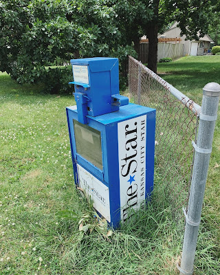 A newspaper box, blue, standing in weeds, next to a chain link fence. This is where we originally picked up the box with permission from The Kansas City Star