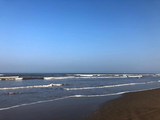 A foto mostra as ondas do mar se espraiando na areia uma após a outra.