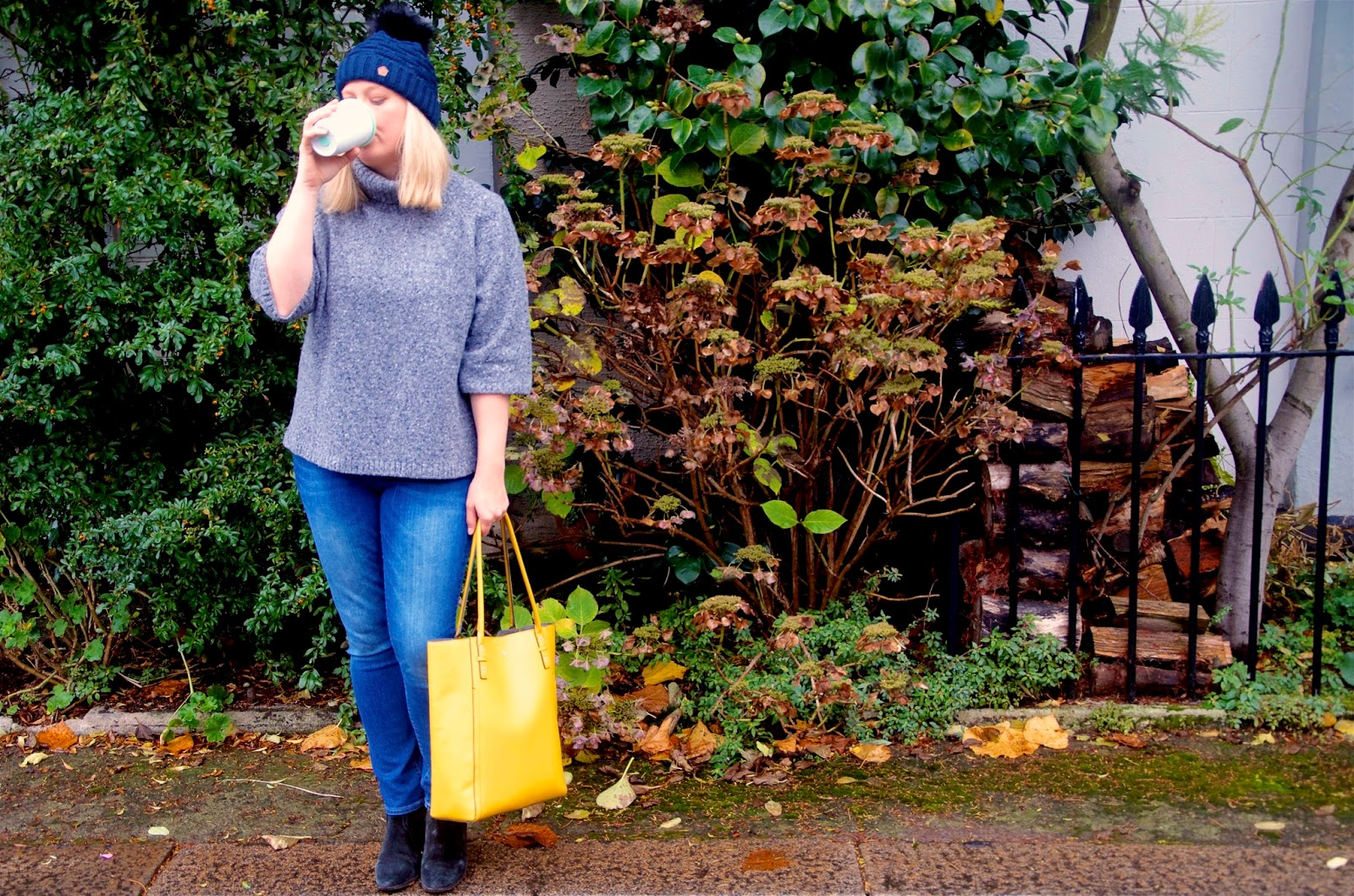 Yellow bag, white coffee cup, grey sweater, skinny jeans, navy hat and black boots.