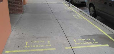 Sidewalk with yellow markings and stenciled lettering, making a box