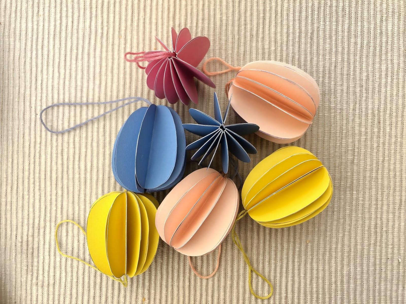 How to make Easter paper decorations in the shape of an Easter egg, perfect for decorating your home for spring, or for creating a pretty seasonal table setting. DIY tutorial craft perfect for when you're stuck inside at home on lockdown. Complete with printable template.
